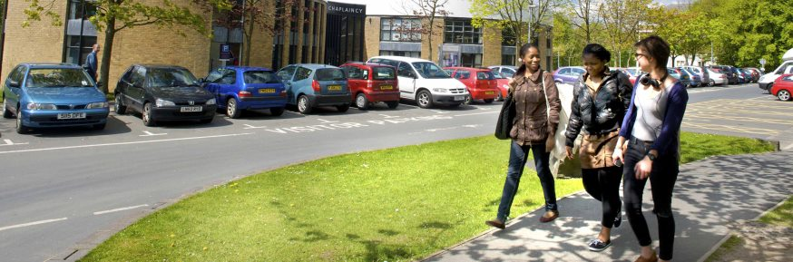 Three females walking in campus car park