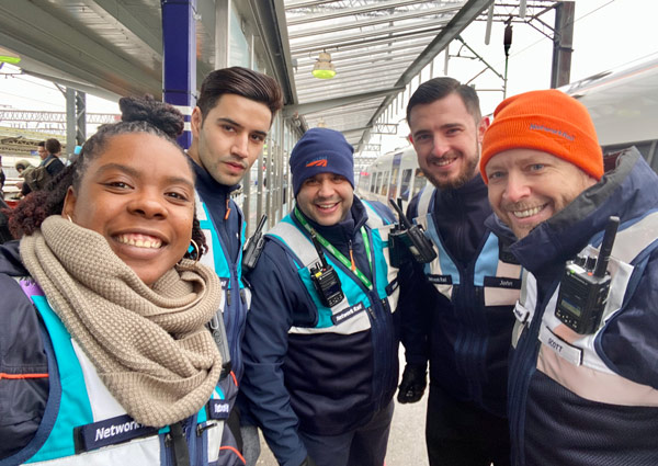 A group of 5 smiling workers on the train platform