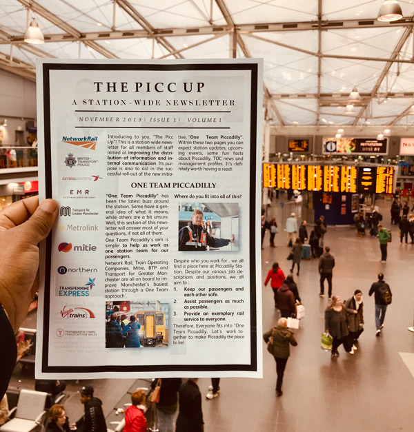 A hand holding a copy of the Piccadilly station staff newsletter
