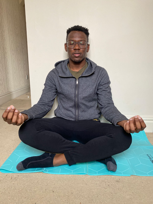 A male student sitting on a yoga mat, crossed legs with eyes closed