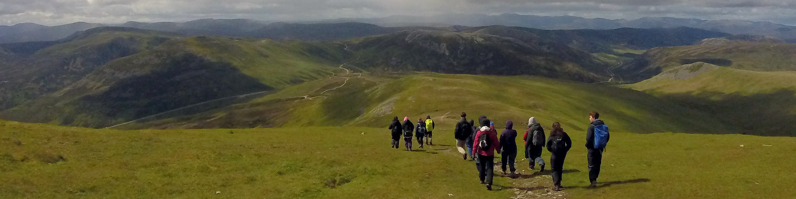 A group of students walk down a Scottish mountain