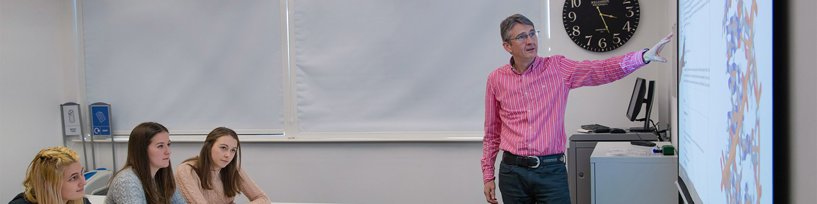 A lecturer stands in front of a white board