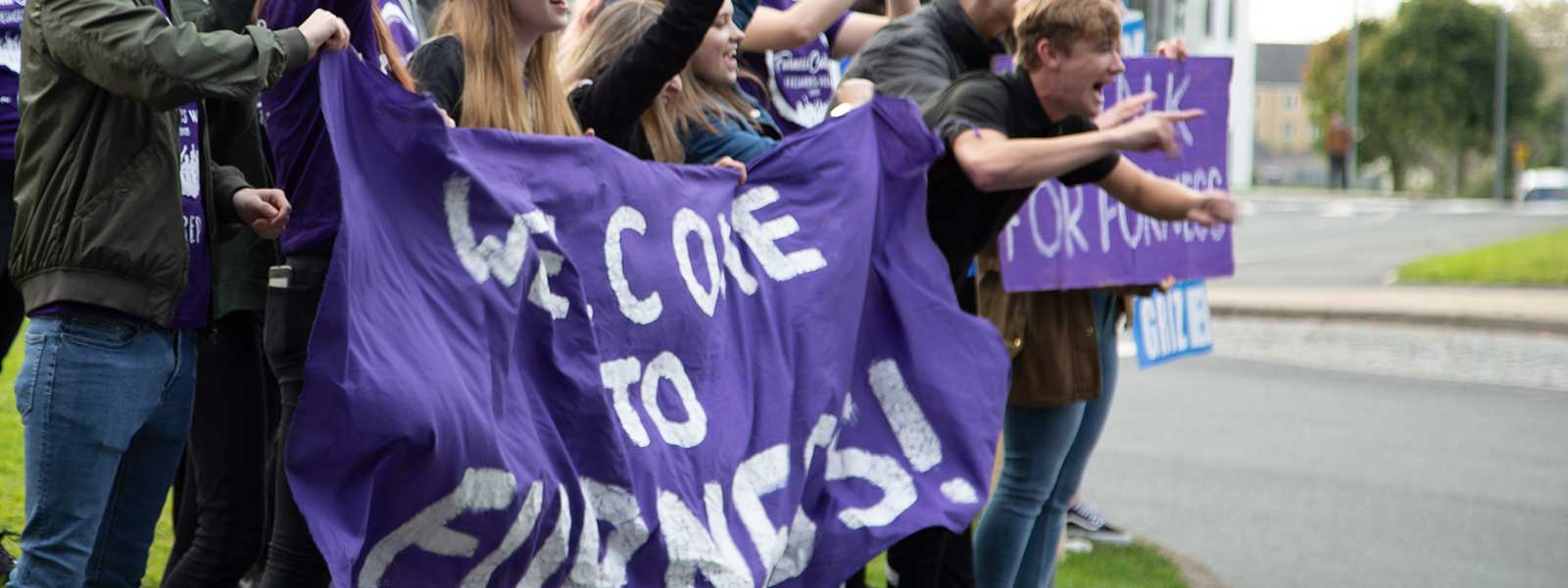 Students holding Furness welcome banners