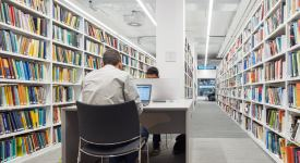Students sat working in the Library between bookshelves