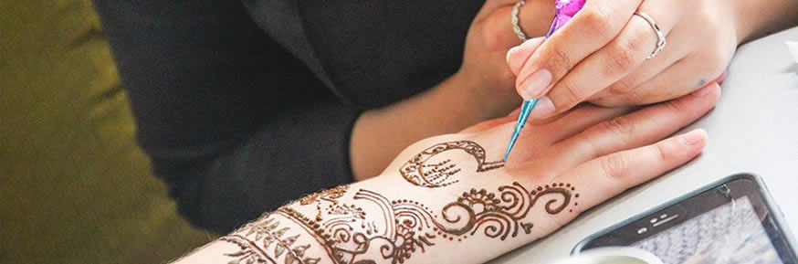 Girl drawing a henna tattoo