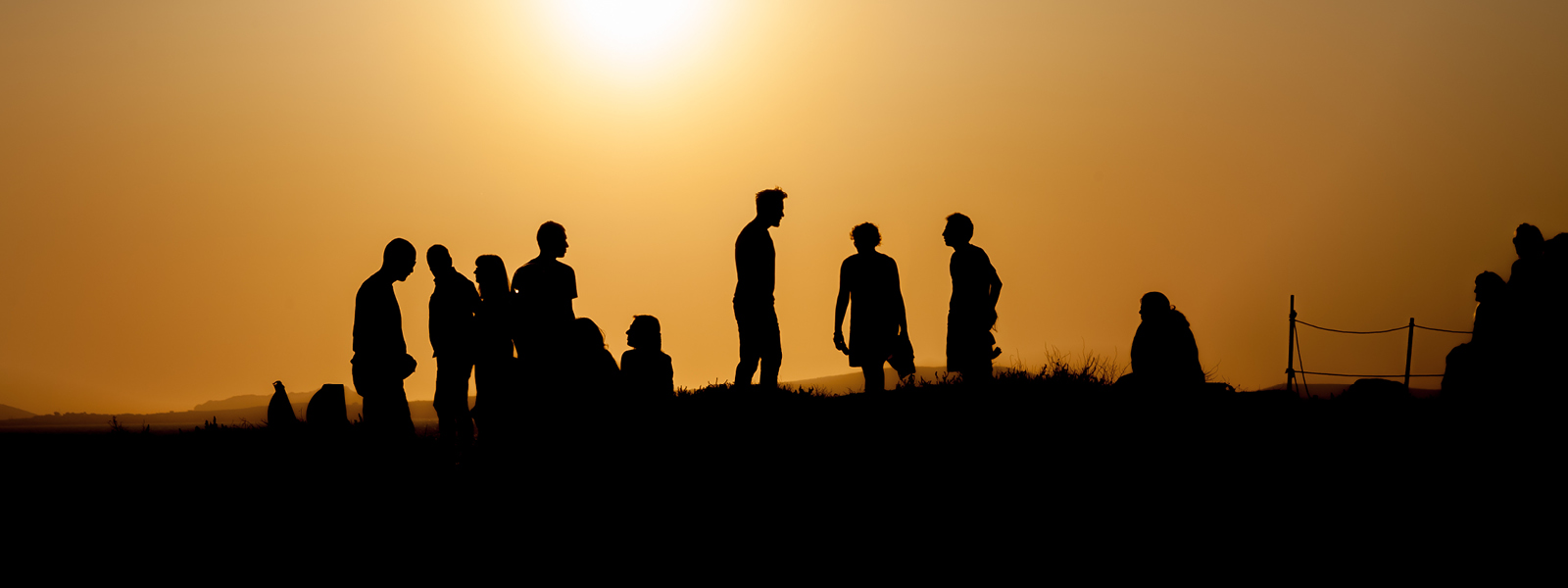Silhouette of a group of people with a sunset in the background