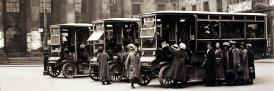 Fleet of battery-powered buses pick up passengers in Market Square for the Caton Road Munitions Works in 1917.