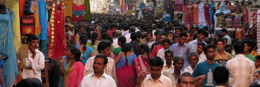 Image of a street in Chennai, India, bustling with people, and stall selling clothes, textiles, etc.