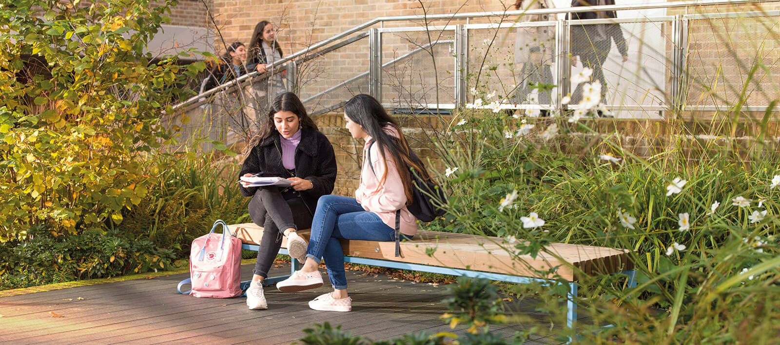 Tow female students sitting on a bench chatting and looking at a notepad