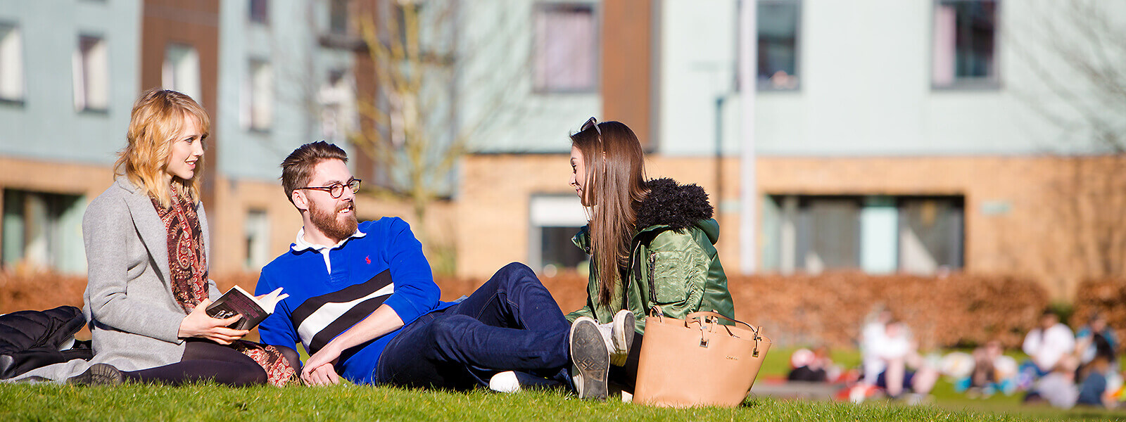 Students sitting on the grass at Lancaster University
