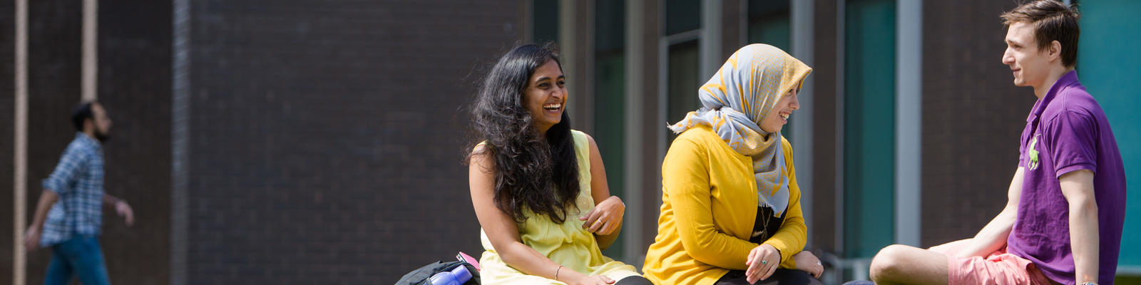 A group of students laughing together sat on the grass at the Lancaster University campus